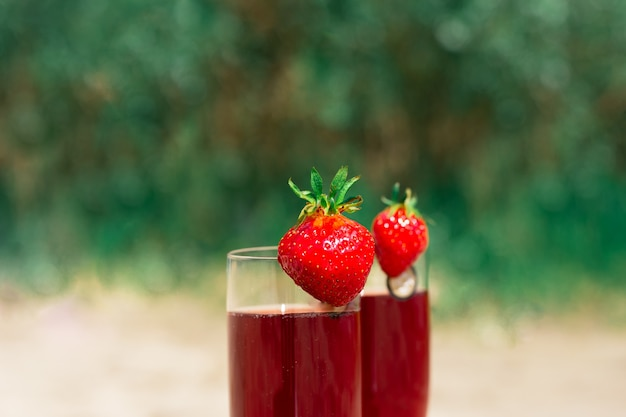 Two crystal glasses with cherry champagne and strawberries summer alcohol drinks background