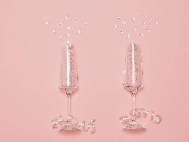 ピンクの背景にシャンパンのスプラッシュを模倣したスパンコール付きの2つのクリスタルグラス。シャンパングラスでお祭りの背景。