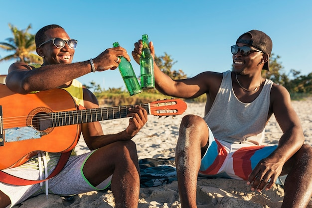 Two cuban friends having fun in the beach with his guitar. friendship concept.