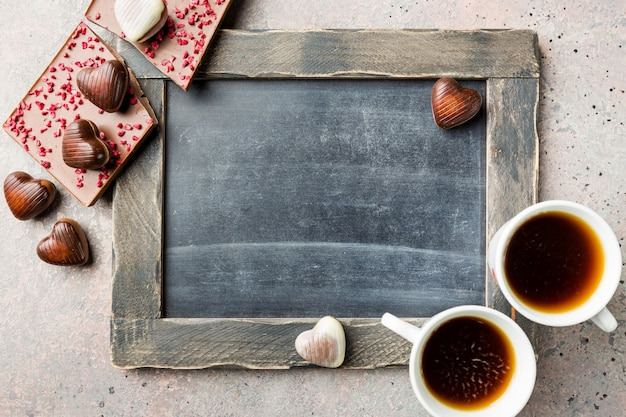 Two cup of coffee and chocolate candies in a heart shape over blackboard background for valentine's day concept. top view