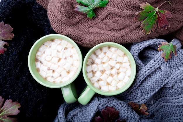 Two cup of coffee or hot chocolate with marshmallow near  knitted.