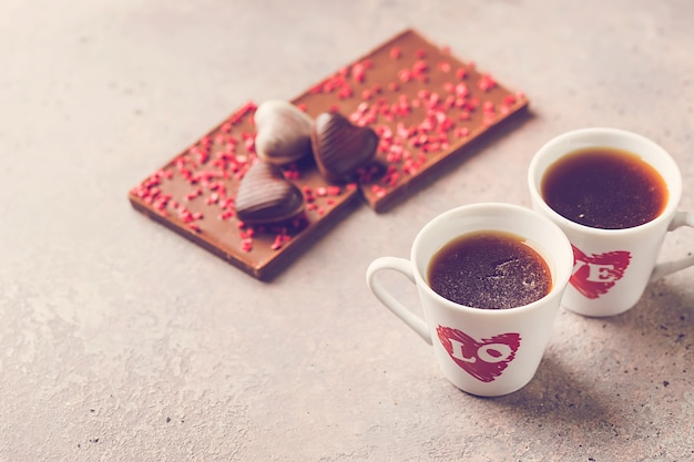 Two cup of coffee with love and chocolate candies in a heart shape over gray background for valentine's day conception