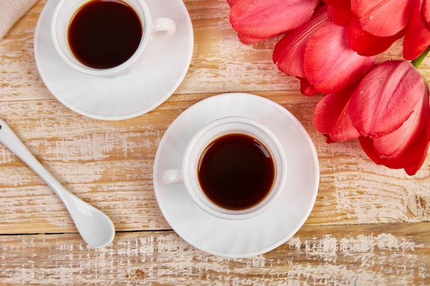 Two cup of coffee with pink tulip flowers