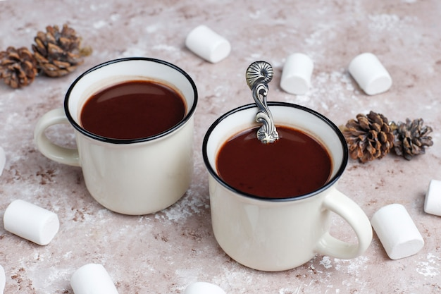 Two cup of hot chocolate with marshmallow on light