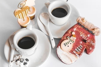 Two cup of coffee and wooden mitt with welcome text and snowman on white backdrop