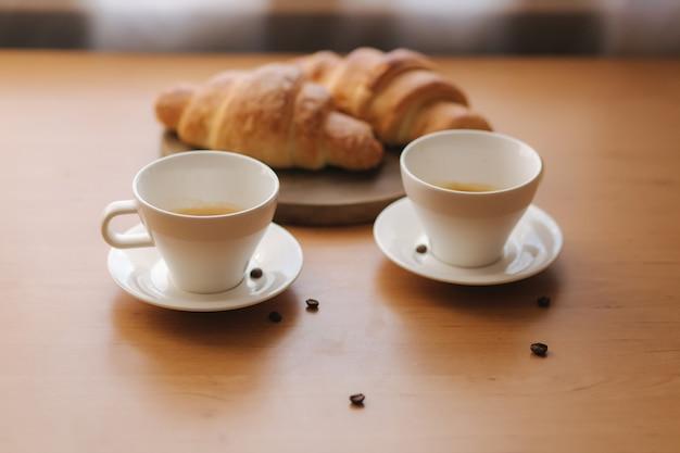 木製のテーブルにコーヒー2杯と焼きたてのクロワッサン2杯。自宅で朝食。