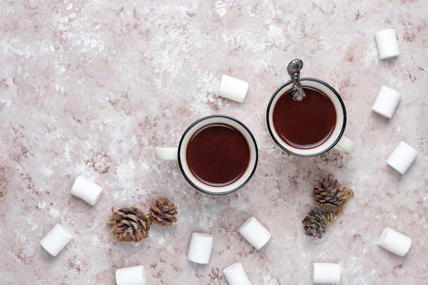 光のマシュマロとホットチョコレートの2つのカップ