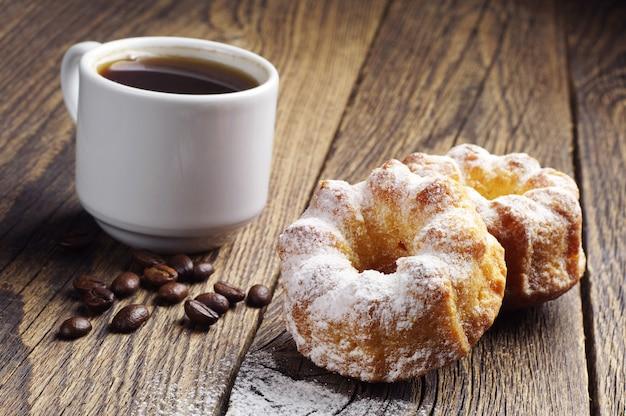 나무 테이블에 두 컵 케이크와 커피 한 잔