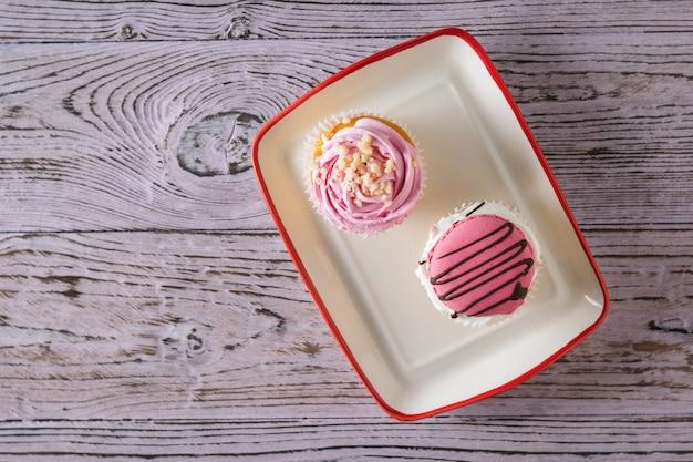 木製のテーブルの上のボウルに2つのカップケーキ