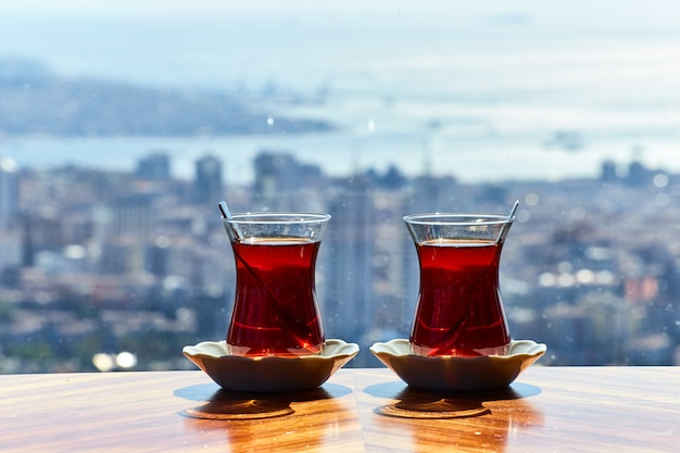 Two cups (armudas) of traditional turkish tea are served on a table against the background of the istanbul cityscape