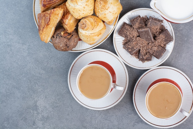 Two cups of aroma coffee with pastries on gray table.