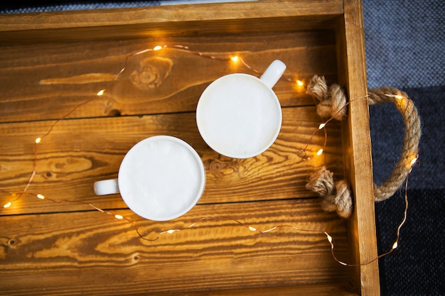 Two cups cappuccino stand on a wooden tray with lights