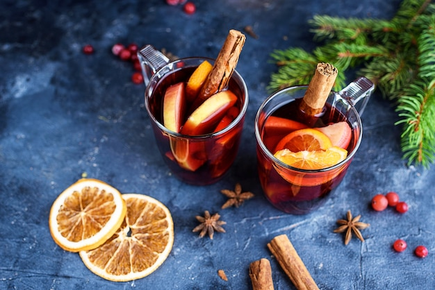 Two cups of christmas mulled wine or gluhwein with spices and orange slices on rustic table top view. traditional drink on winter holiday. new years content