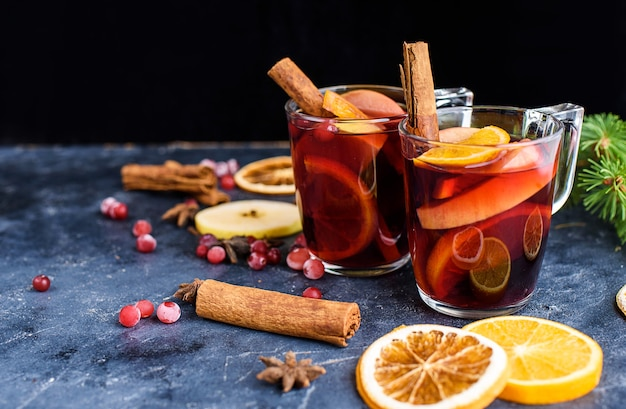 Two cups of christmas mulled wine or gluhwein with spices and orange slices on rustic table