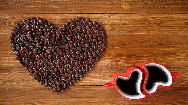 Two cups and coffee beans in the form of a heart on a wooden background. valentine's day, 3d rendering illustration.
