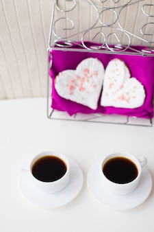 Two cups of coffee and biscuits in the form of heart on a pink napkin