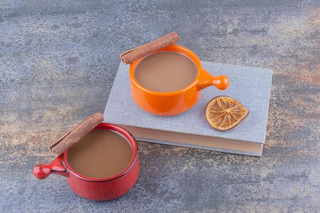Due tazze di caffè, libro e bastoncini di cannella. foto di alta qualità