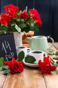 Two cups of coffee, a bouquet of red roses on a wooden background and a greeting card with text.
