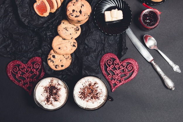 Two cups of coffee, cappuccino with chocolate cookies and biscuits near red hearts on black table