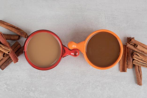Due tazze di caffè e bastoncini di cannella sulla superficie di marmo