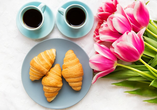 Two cups of coffee, croissants and a bouquet of pink tulips, beautiful morning