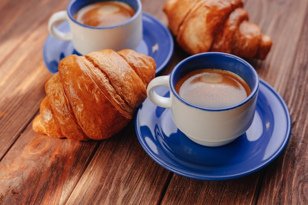 Two cups of coffee and croissants on a wooden background, good light, morning atmosphere