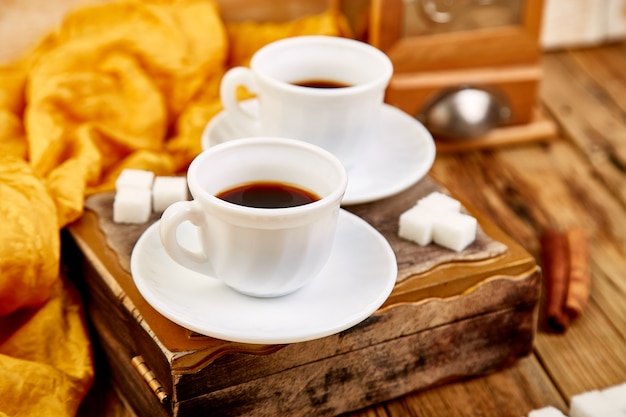 Two cups of coffee espresso near sugar cube on rustic wooden table.