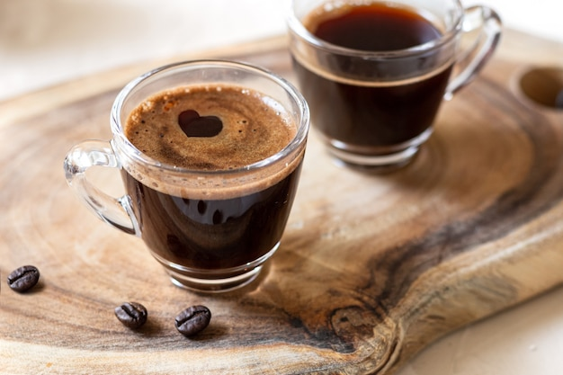 Two cups of coffee espresso with heart shape and coffee beans on wooden background. close up