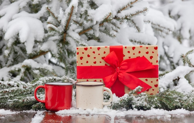 Two cups of coffee and gift box on wooden table in snow