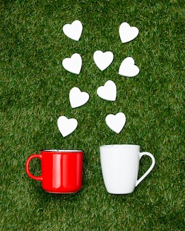 Two cups of coffee and heart shapes on green grass.