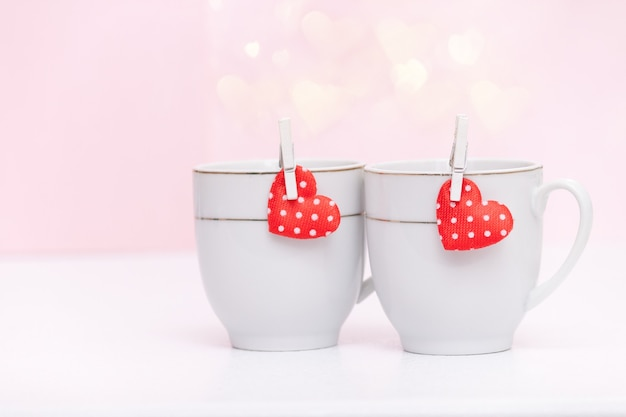 Two cups of coffee, hearts bokeh, valentine's concept.