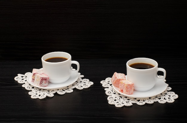 Two cups of coffee on the lace napkins and  turkish dessert on a black