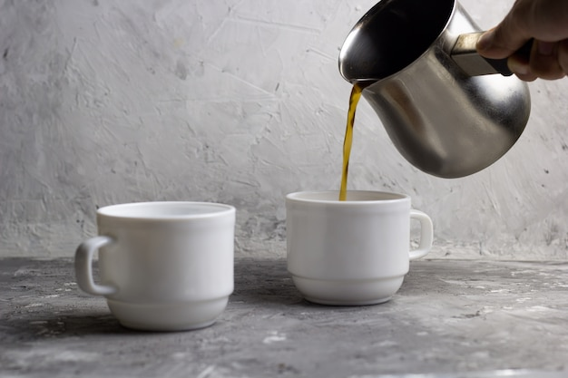 Two cups of coffee, man  pours coffee from cezve , concrete background