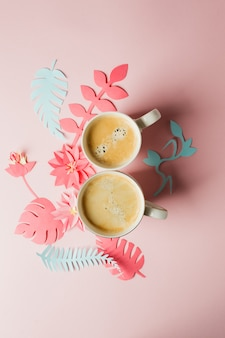 Two cups of coffee and modern origami handcraft paper flowers copy space