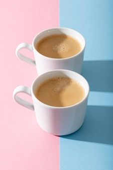 Two cups of coffee on a pastel pink and blue background, photography with contrast shadow