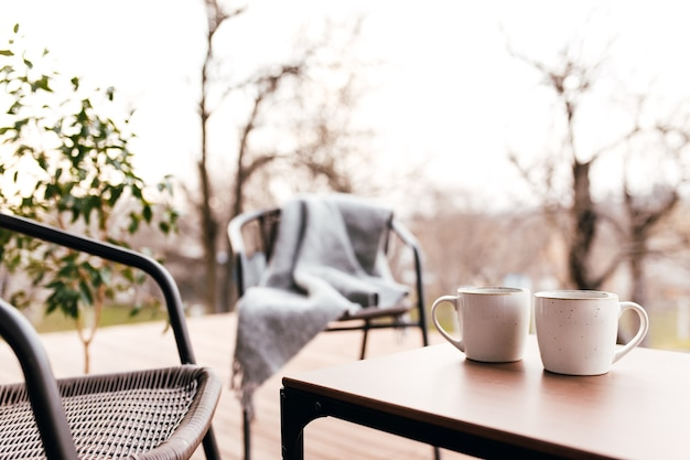 Two cups of coffee on the table on the wooden brown terrace during evening sunset. relaxation, lovers romantic evening concept
