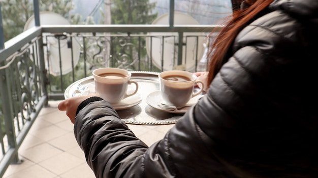 Two cups of coffee on a tray in the hands of a girl. a woman with cups in her hands enters the hotel's balcony in the morning. drink coffee with mountain and forest views.