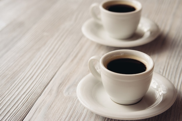 Two cups of coffee on a white wooden table