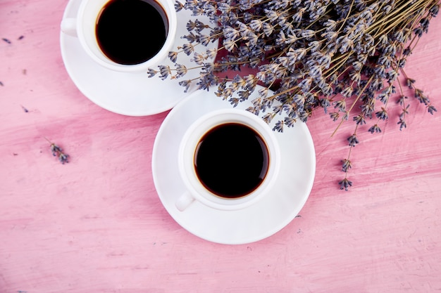Two cups of coffee with bouquet of flowers lavender