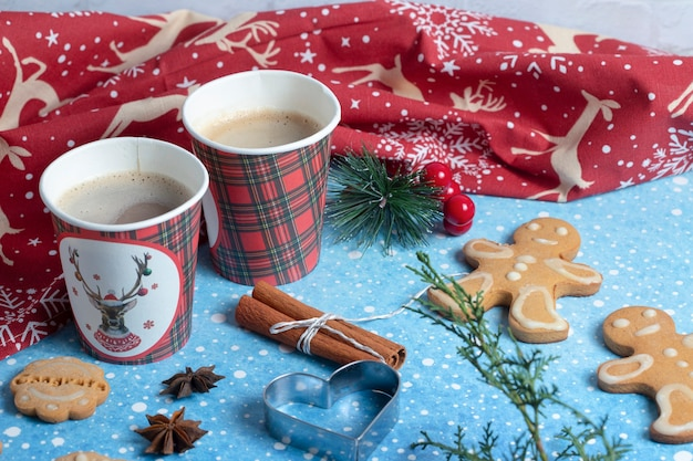 Two cups of coffee with cinnamon sticks and cookies over blue