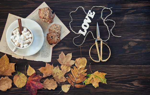 Two cups of coffee with cookies with autumn colored leaves.