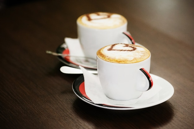 Two cups of coffee with heart pattern in a white cups on wood table