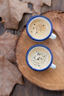 Two cups of coffee with leaves on wooden background