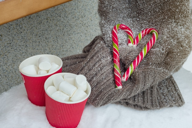 Two cups of coffee with marshmallow, two christmas candy canes.