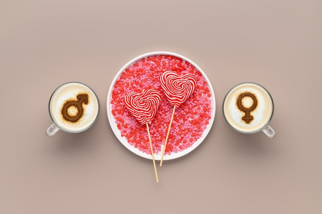 Two cups of coffee with symbols of male and female on whipped milk foam and lollipops in heart shape on white plate. beige background. concept romantic date on valentine's day. flat lay