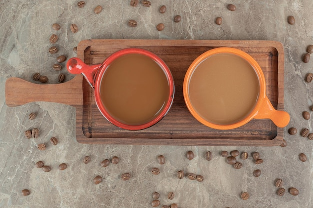 Two cups of coffee on wooden board with coffee beans