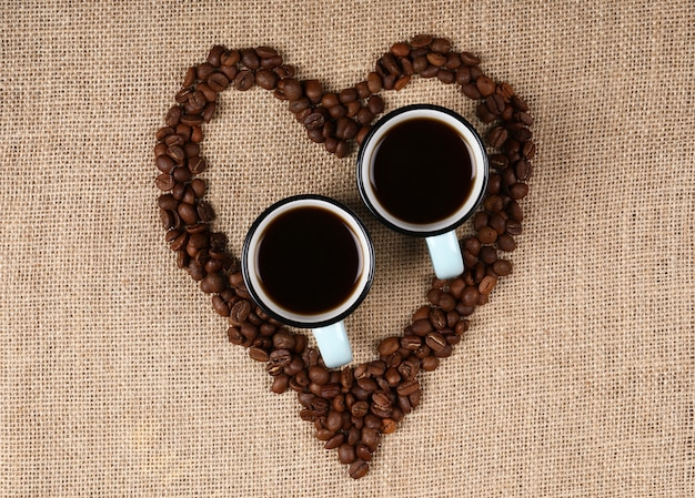 Two cups of espresso in a heart shaped coffee beans.