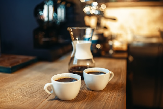 Two cups of fresh black coffee on wooden counter