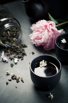 Two cups of green jasmine tea set peonies, closeup shot. dark style photo.