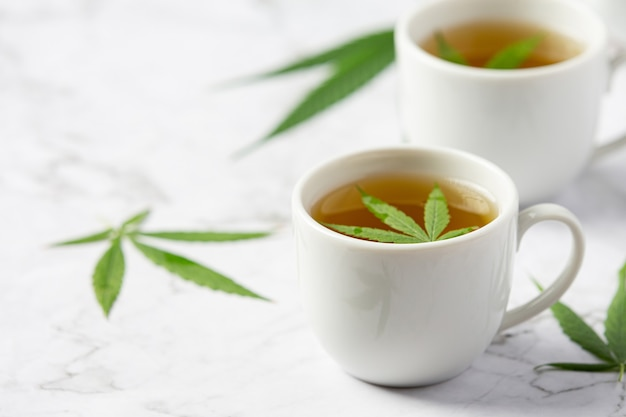 Due tazze di tè alla canapa con foglie di canapa messe sul pavimento di marmo bianco